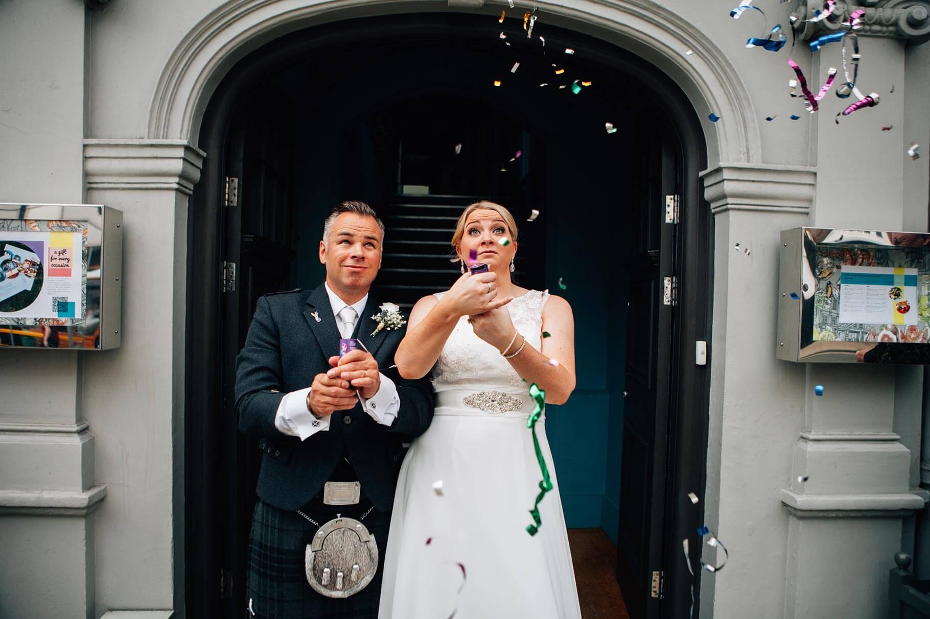 Fun confetti shooter photo of wedding couple