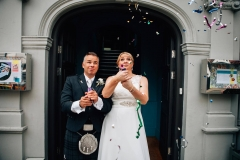 Fun confetti shooter photo of wedding couple