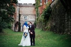 Wedding couple in front of castle and bride with blue hair