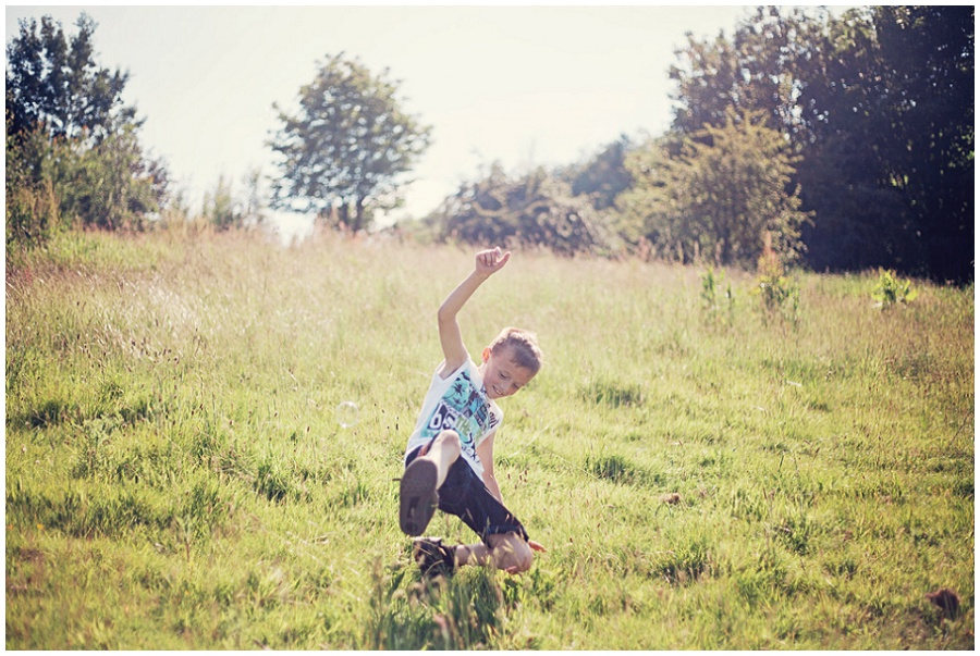 Photography of child playing in field